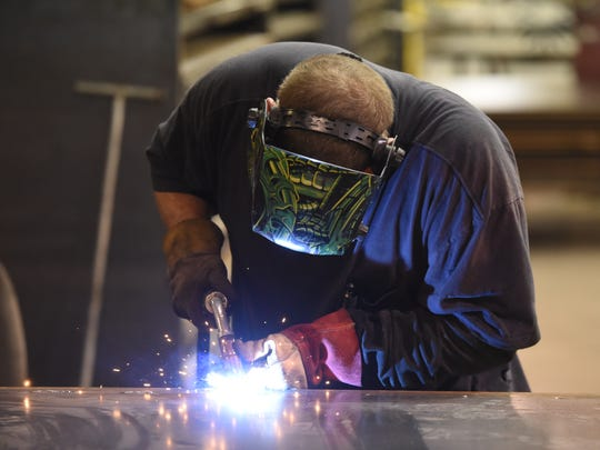 Johnny Davis welds at American Epoxy Scientific in Mountain Home on Wednesday. Davis learned to weld after being laid off at the plant last year.