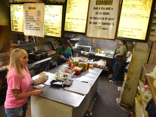 "Mary Harden, left, co-owner of Beatty Street Grocery, gathers food for an order as employees cook and slice. Longtime employee Joanie Buckley said of the fast-paced diner environment, ""You can't be thin-skinned down here."""
