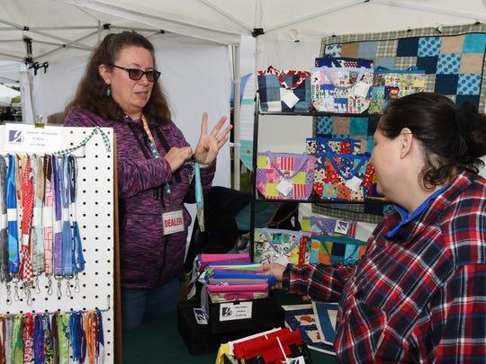 Jennifer Larrabee, left, owner of Jeneric Bags, talks