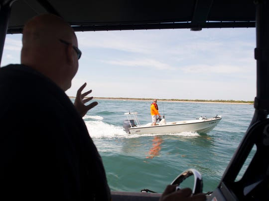"""Martin County Sheriff's Office Deputy Mike Joseph (left) chats with boater John Barca as they head into the Indian River Lagoon on May 11 through the St. Lucie Inlet in Martin County. Joseph and other deputies will be heavily patrolling the waterways around the Memorial Day holiday, where Joseph estimates over a thousand people will be celebrating at the Stuart sandbar. """"You want everybody to have a good time, but you want everybody to be safe, too,"""" Joseph said. For a holiday, the focus is """"sandbars and safety."""""""