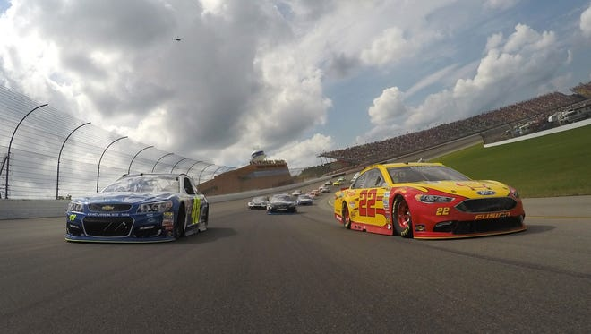 Joey Logano, driver of the #22, and Jimmie Johnson, driver of the #48, lead the field during pace laps prior to the NASCAR Sprint Cup Series Pure Michigan 400 at Michigan International Speedway on Aug. 28, 2016 in Brooklyn.