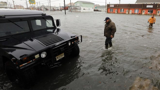 North Wildwood, N.J. Office of Emergency Management coordinator Bob Matteucci, center, and Mayor Patrick Rosenello walk through flood waters at the city's firehouse at 4th and New Jersey Aves., Saturday, Jan. 23, 2016. A winter storm created near record high tides along the Jersey Shore, surpassing the tide of Hurricane Sandy according to North Wildwood city officials.