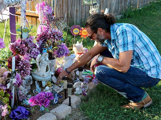 Vern Landavazo cleans off a marker left at a memorial for his daughter, Lauren Landavazo, on Aug. 28, 2017. Lauren was murdered on Sept. 2, 2016 walking home from school.