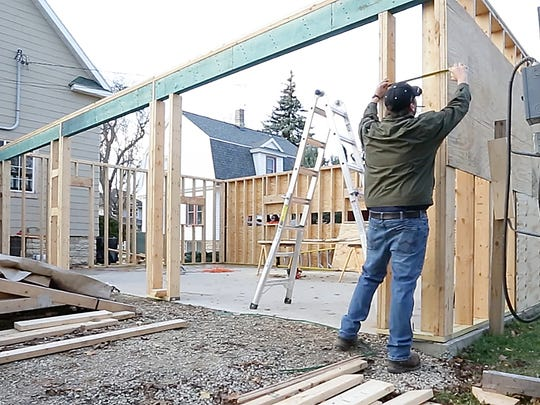Students and instructors from a Fond du Lac High School Building Construction class erect a garage Nov. 29, 2016, as part of the class.