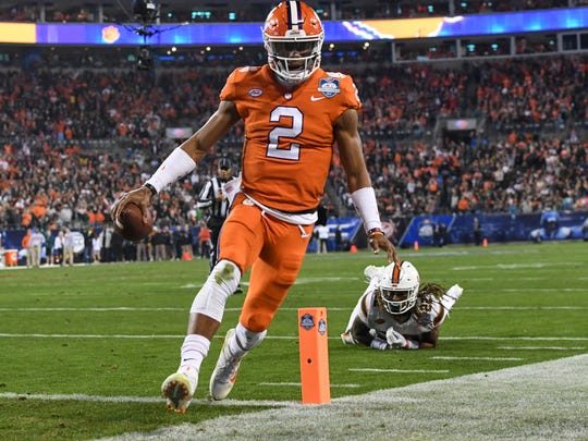 Clemson quarterback Kelly Bryant scores by Miami free safety Sheldrick Redwine (22) during the first quarter of the ACC championship game against Miami at Bank of America Stadium in Charlotte on Saturday, December 2, 2017.