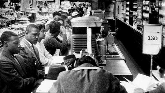 """The """"closed"""" sign goes up as soon as black colleges students sit at the counter of the downtown Woolworth's on Feb. 27, 1960. Later at the store, a group of white boys attacked two black demonstrators."""