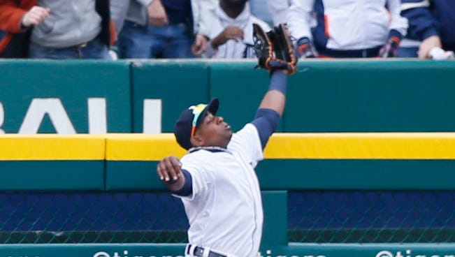 Detroit Tigers outfielder Yoenis Cespedes takes a home run away from Minnesota's Kurt Suzuki during the third inning Monday, April 6, 2015 in Comerica Park.