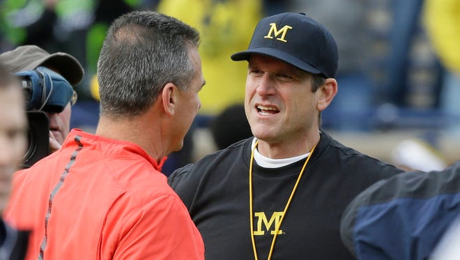 Ohio State football coach Urban Meyer meets with Michigan coach Jim Harbaugh, right, before a game Nov. 28, 2015, in Ann Arbor.
