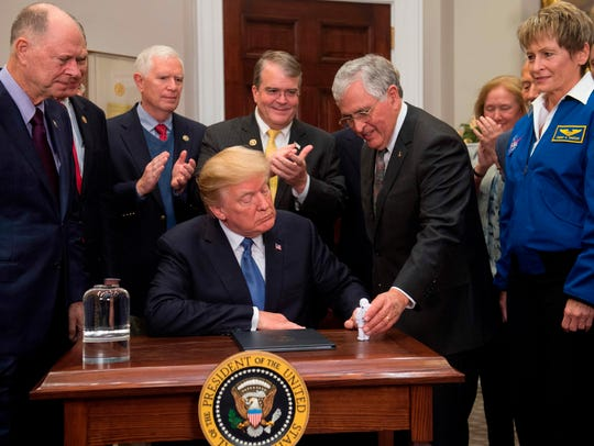 WASHINGTON -- President Donald Trump looks at an astronaut toy alongside former Senator and Apollo 17 Astronaut Jack Schmitt (2nd R), and NASA Astronaut Peggy Whitson (R) after a signing ceremony in December for Space Policy Directive 1, with the aim of returning Americans to the Moon, in the Roosevelt Room at the White House.