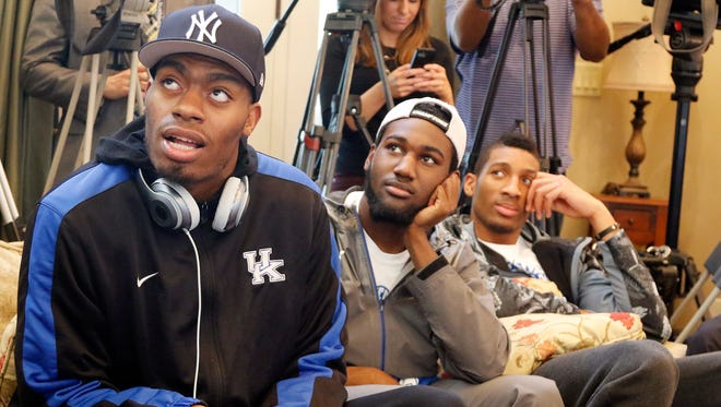 From left, Dakari Johnson, Dominique Hawkins, Marcus Lee and other members of Kentucky's men's basketball team watch the NCAA college basketball tournament selection show at the home of head coach John Calipari in Lexington, Ky. March 15, 2015