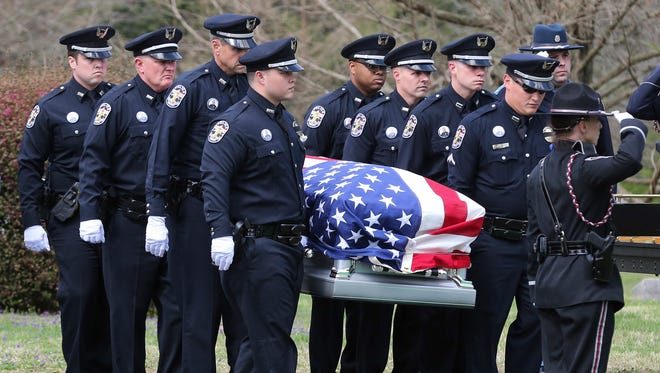LMPD officers carry the casket fallen officer Nick Rodman at Cave Hill Cemetery.