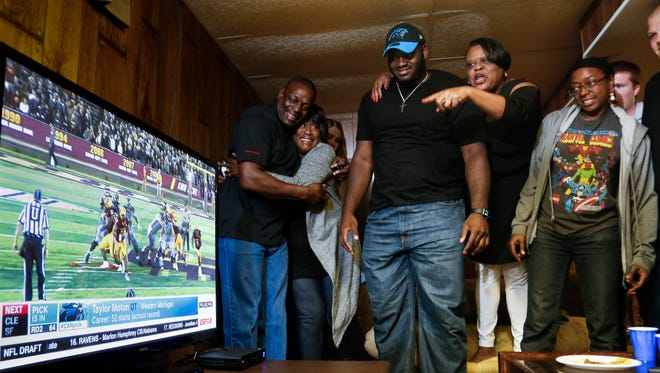 Friends and family of Okemos native and Western Michigan University football standout Taylor Moton, center, react upon viewing the official announcement that the Carolina Panthers had selected Moton in the second round of the NFL draft Friday night. home in Okemos. From left:  Moton's dad Delbert Husband and aunt Gerry Stroman, mom Sonya Gunnings-Husband, and sister Shy Husband.