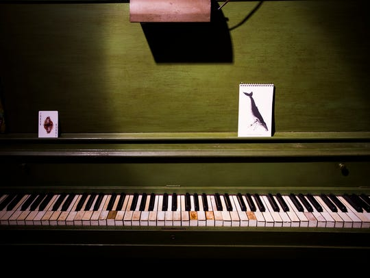 A green upright piano sits in the library and bookstore