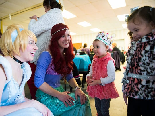 Black Rose Rollers team members Katie Dennis, left, and Courtney Kapraun, dressed as Cinderella and the Little Mermaid, greet sisters Giovanna Kourliouros, 2, and Anastasia Kourliouros, 3, at right, during an Afternoon Tea with Alice and the Princesses fundraiser event Saturday Feb. 13, 2016 at the Hanover YWCA.  Ticket sales and a raffle helped raise funds for the Black Rose Rollers which helps finance the team's insurance and travel costs for the upcoming season.