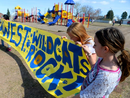 West Elementary students hold a paper banner ahead of the dedication for their new playground structures on Thursday afternoon. The West Elementary PTA raised $30,000 over seven years to purchase the playground equipment.