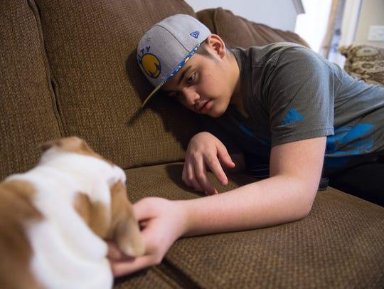 Jaaziel Daniel Alicea, 14, plays with his puppy, Jay,