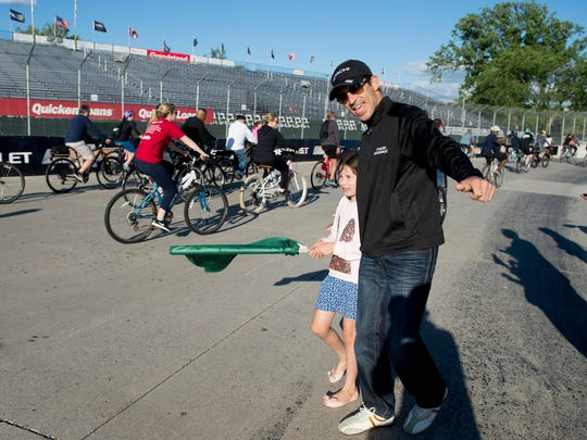 Team Penske Verizon IndyCar Series driver Helio Castroneves and his daughter Mikaella, 7, wave a green flag to welcome the Slow Roll onto Detroit's Belle Isle on May 31, 2017.