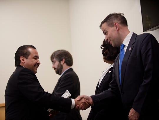 Samuel Uribe shakes the hand of James McCament, USCIS