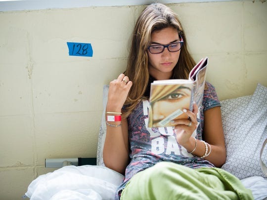 Azul Veron, of Argentina, reads a book while staying