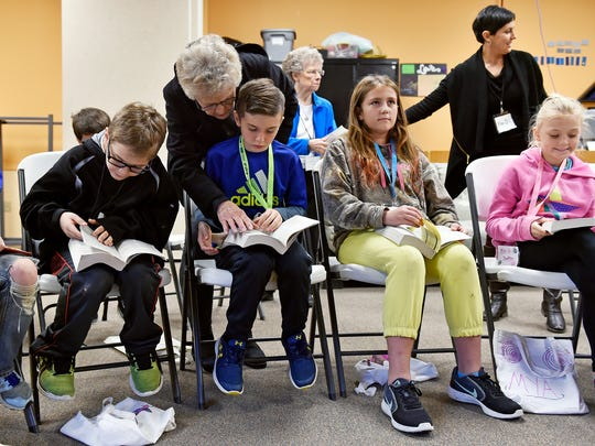 Volunteer Carol Corwell, back, helps Hunter Naugle, 10, find a verse in his Bible during released time Thursday, Nov. 9, 2017, at Valley View Alliance Church in Hellam Township. Released time is time set aside during school hours for students to voluntarily receive religious education that is off-campus and receives no public funding, per a 1952 U.S. Supreme Court decision. More than a dozen Kreutz Creek Elementary third-, fourth- and fifth-grade students come for an hour of released time at Valley View Alliance Church once a week, in a program operated by Joy El Ministries.
