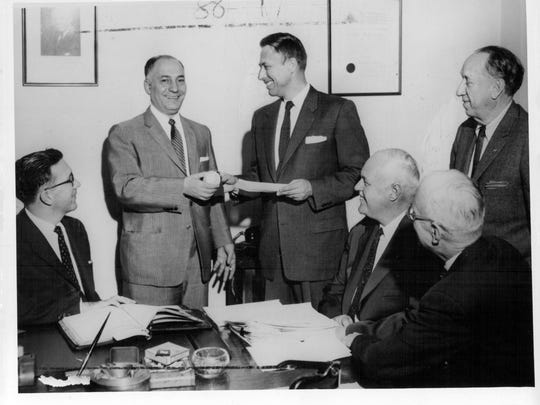 Civic leader Morrie Silver, standing at left, seals the deal with St. Louis Cardinals assistant GM Bing Devine to purchase the Red Wings for Rochester Community Baseball in February 1957.
