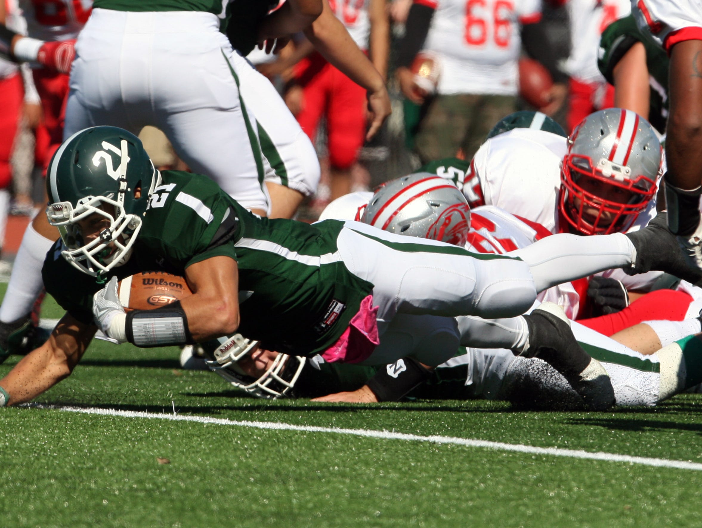 Action photos from the Perth Amboy High School at St. Joseph football game held at St. Joseph's new turf field in Metuhen on Saturday October 10, 2015. Here St. Joseph's # 21-Emmanuel Resto dives head fro first down yardage during the first half of play in Metuchen.