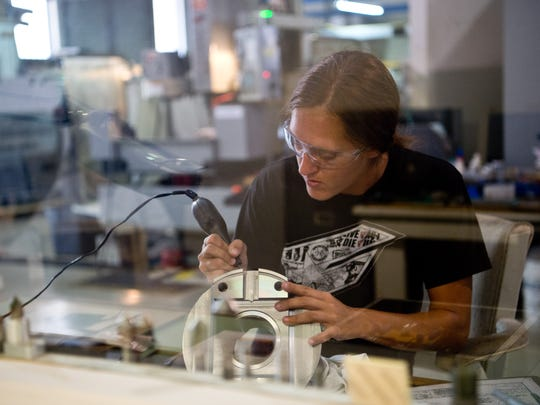 Nicole Button, of Stuart, engraves serial numbers on