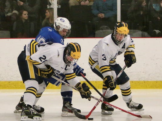 Hartlands John Nagel and 3 Daniel Smith muscle the puck away from Lakelands .jpg