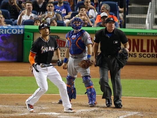 Miami Marlins' Giancarlo Stanton, left, watches his