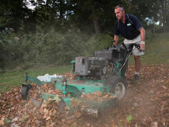 Landscaper Tim Downey of Aesthetic Landscape Care of Hastings, demonstrates how to create mulch using a commercial mower fitted with special blades and a simple modification to block the mower's discharge chute. The demonstration took place Oct. 1, 2013 at Redmond Park in Yonkers. ( Joe Larese / The Journal News )