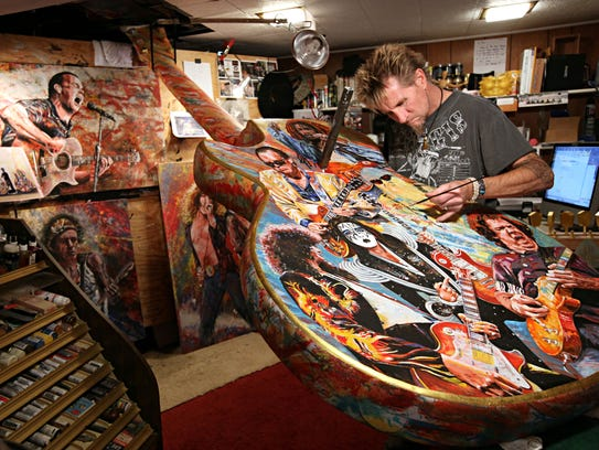Artist Tom Noll works in the basement of his home painting