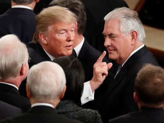 Trump gestures as he passes Tillerson after his address