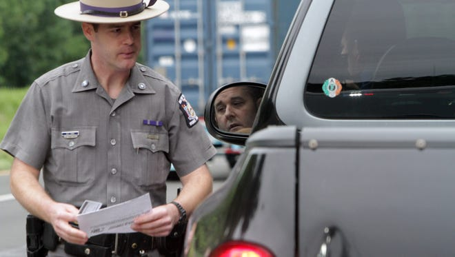 New York state Trooper Matthew Yorke talks to a motorist who was using a cellphone while driving in Somers, N.Y., on July 25, 2013. Distracted driving has recently become a top priority for New York Gov. Andrew Cuomo, who just signed a law that stiffens the penalties for texting while driving.