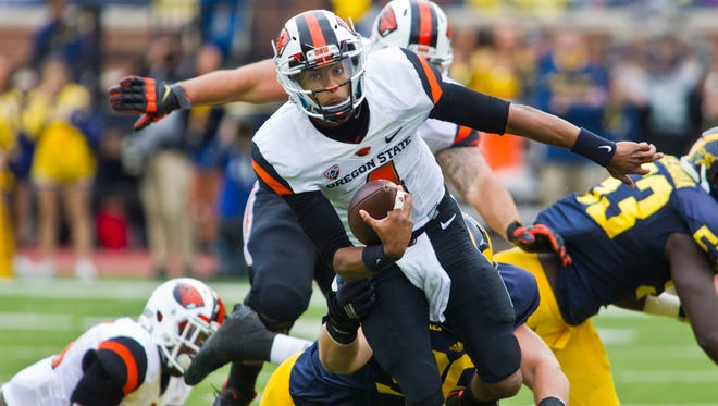 Oregon State quarterback Seth Collins (4) tries to evade tackles on a carry in the second quarter of an NCAA college football game against Michigan in Ann Arbor, Mich., Saturday, Sept. 12, 2015.