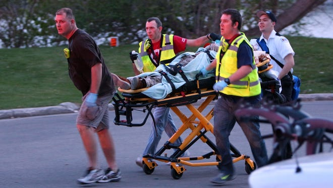 Authorities move a shooting victim to an ambulance on the east side of the Trestle Trail Bridge in the City of Menasha on May 3, 2015. Police confirmed there are four fatalities, including the shooter, and one injured.