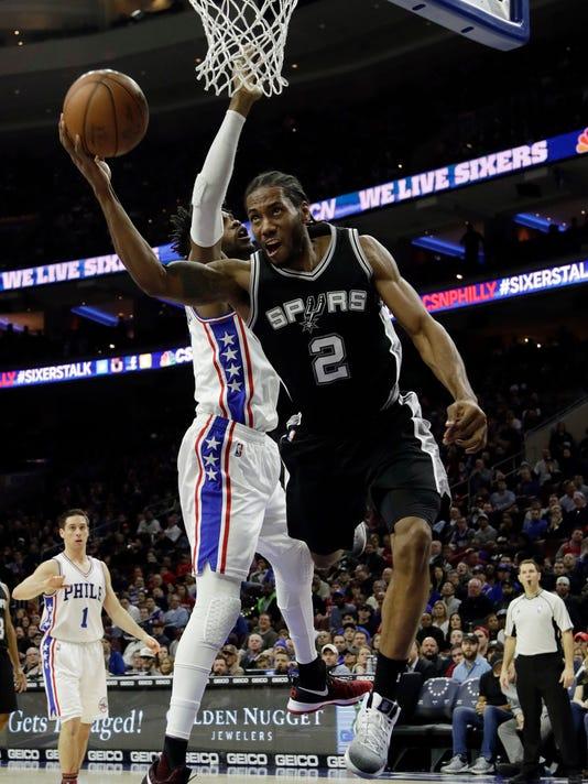 San Antonio Spurs' Kawhi Leonard, right, tries to get a shot past Philadelphia 76ers' Nerlens Noel during the second half of an NBA basketball game, Wednesday, Feb. 8, 2017, in Philadelphia. San Antonio won 111-103. (AP Photo/Matt Slocum)