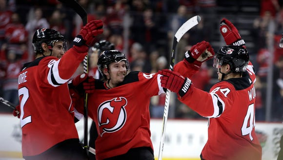 New Jersey Devils' John Moore, left, Sami Vatanen,