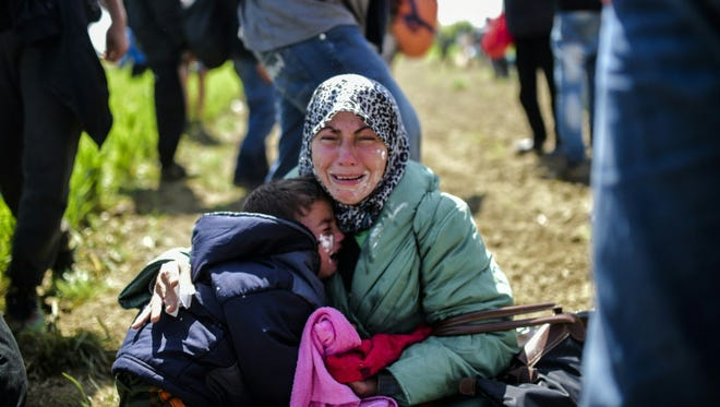 Refugees and migrants hurt by tear gas on April 10, 2016, at their Idomeni camp in the northern Greek border with Macedonia.