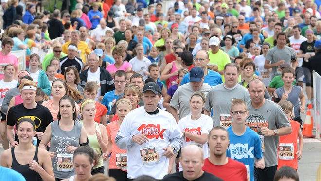 Runner Mark Pabian (9211) of Manitowoc runs through the starting line among the more than 16,000 participants at the 2015 Bellin Run.
