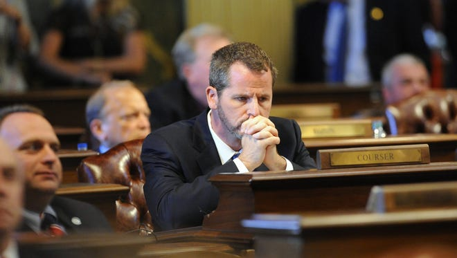 State Rep. Todd Courser waits at his desk as  votes roll in  on whether or not to expel Rep Cindy Gamrat and  Courser in the House of Representatives on Sept. 10.