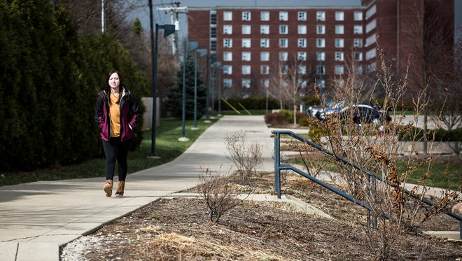 "A student walks on the Ball State University ""Cow Path"" that could be widened to include a separate bike lane."