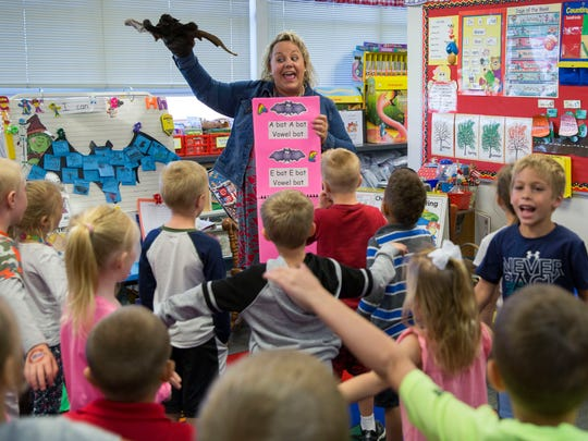 "Mindy Matthews, a kindergarten teacher at Oak Hill Elementary, sings the ""Vowel Bat"" song with her students after reading them the book ""Stellaluna."""