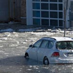 Car of Asbury Park Press photographer Peter Ackerman stuck in flood waters as bay high tide moves in.