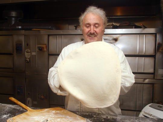 Nick Azzaro, owner of Papa's Tomato Pies, makes a pizza.