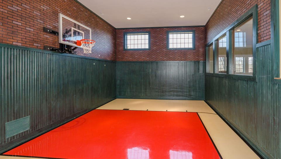 An indoor basketball court comes with a mounted rim.