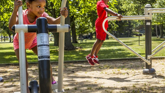 Cousins Alana Lowe, 5, left, and Darius Washington, 11, ignore the heat and humidity to burn off some energy Monday, June 29, 2020 on exercise equipment at Glen Oak Park.
