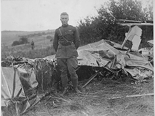 Frank Luke Jr. stands amid the wreckage of one of his