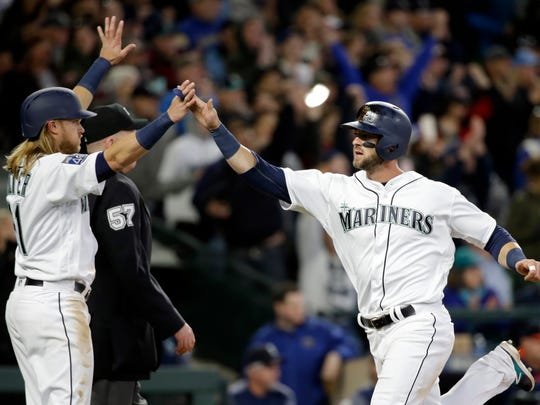 Seattle Mariners' Taylor Motter (left) greets Mitch Haniger at home after both scored on a single by Nelson Cruz against the Houston Astros in the fifth inning of Monday's home opener.