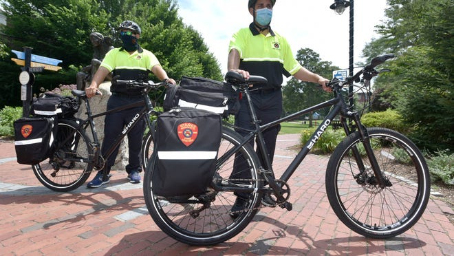 Nik Omerzu, left, and Jack Riley of the Hyannis Fire Department patrol Main Street on bicycles. The department has enacted bicycle patrols this summer that will be in effect on Fridays and Saturdays through Labor Day.