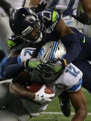 Lions receiver Andre Roberts is tackled by Seahawks